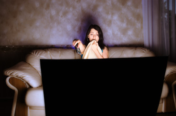 scarried beautiful girl watching TV on a couch