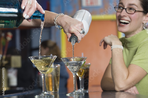 View of a young woman laughing at the bar counter.