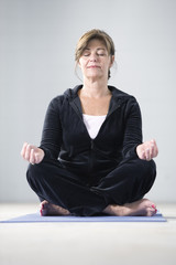 Portrait of a mature woman sitting in lotus position.