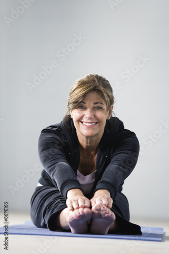 Portrait of a mature woman stretching.