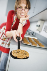 Portrait of a woman holding baked  chololatechip cookie .