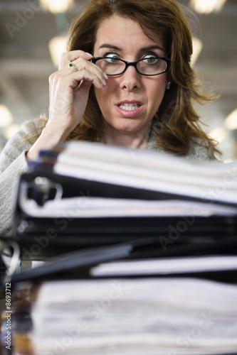 View of a frustrated woman looking at files.