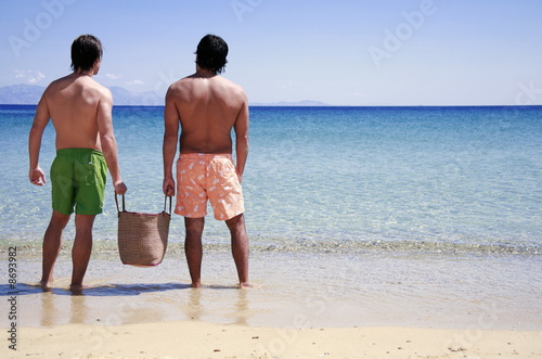 Two men on the beach looking out to sea