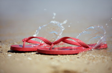 Flip flops on the beach with water splashing