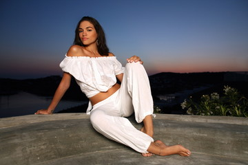 Young woman in white outfit on terrace with a view