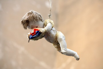 Old doll holding Viewmaster hanging in the air