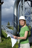 Woman engineer or architect with white safety hat, drawings and poster