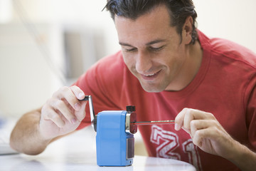 Man indoors using pencil sharpener smiling