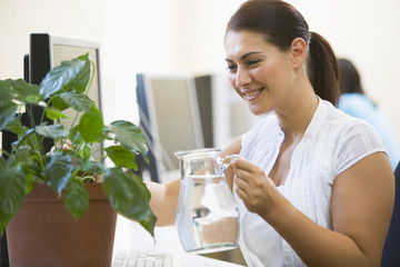 Woman in computer room watering plant smiling