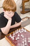 Red head boy playing chess