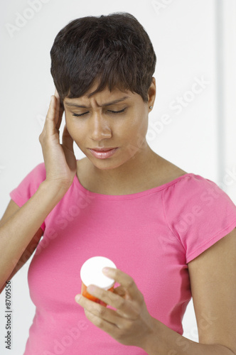Woman with hand on head, holding pill bottle indoors