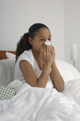 Girl 7-9 blowing nose in bed