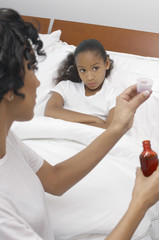 Nurse pouring medication for girl 7-9 lying in bed