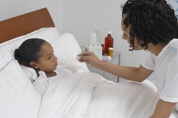 Nurse taking temperature of girl 7-9 lying in bed