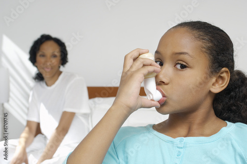 Nurse watching girl 7-9 using inhaler in hospital