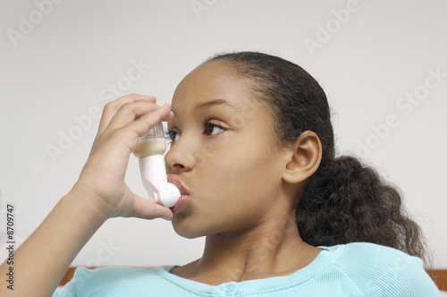 Girl 7-9 using inhaler in hospital