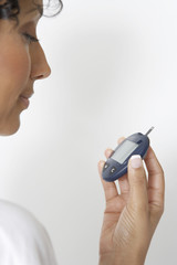 Woman checking diabetes test, close-up, studio shot