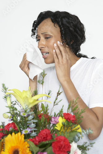 Woman with allergy holding tissue, near flowers, studio shot