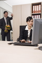Male office worker about to surprise female colleague with flowers