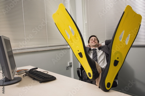 Office worker at desk wearing swim flippers