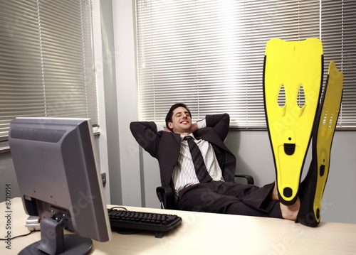 Office worker at computer wearing swim flippers