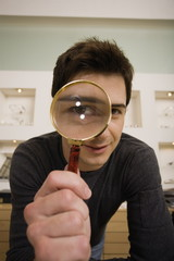 Man with magnifying glass on eye