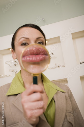 Woman with magnifying glass on mouth