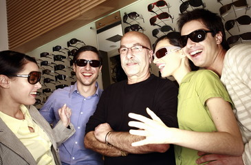 Two couples posing with sunglasses in store with shopkeeper