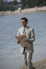 Businessman on beach with a newspaper