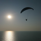 paraglider on sunset flying over the sea