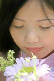 Serene Asian Female Smelling Flowers poster