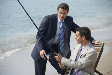 Businessmen on beach fishing