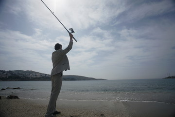 Businessman on beach fishing