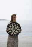 Businesswoman on beach with dartboard