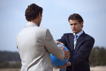 Businessmen on beach holding globe