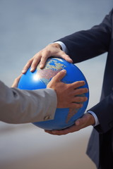 Businessmen's hands grasping globe