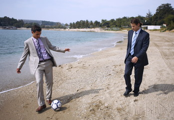 Businessmen on beach playing soccer