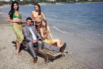Businessman on beach with three women