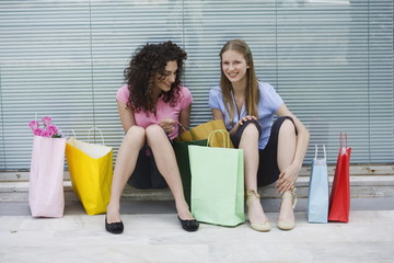 Two women sitting with shopping bags