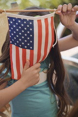Girl hiding behind American flag