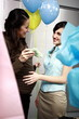Pregnant office worker with colleague at party