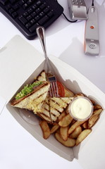 Sandwich in take out carton next to phone on office desk