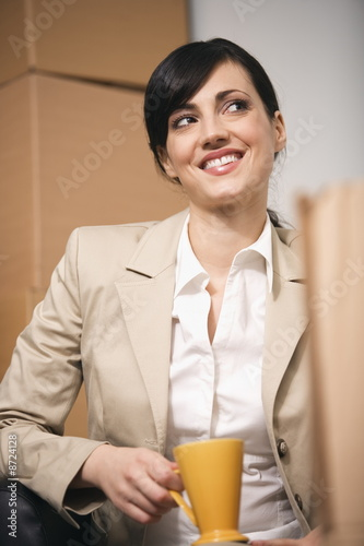 Businesswoman with a cup of coffee among boxes