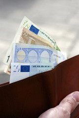 Closeup of hand holding wallet with euros