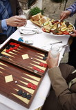 Closeup of businessmen at taverna with backgammon;appetizers;and ouzo