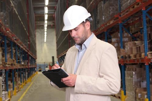 pracownik robiący notatki w magazynie
