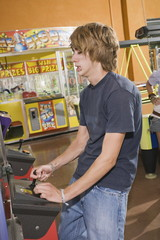 Male teenager playing game in arcade