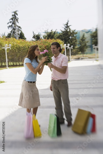 Couple with shopping bags;man offering roses