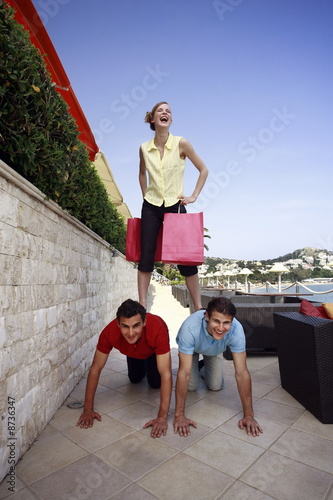 Woman with shopping bags standing on men