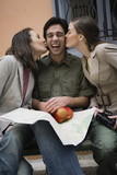 Man on bench being kissed by two women